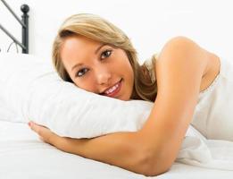 vrolijke vrouw liggend op bed foto