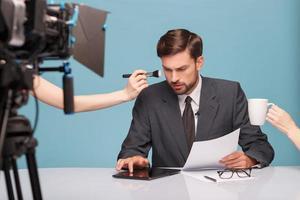 vrolijke mannelijke verslaggever voordat hij wat nieuws vertelde foto