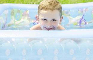 vrolijke kleine jongen in het zwembad foto