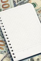 Kladblok en dollars met kopie ruimte foto