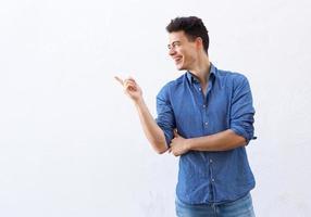 lachende jonge man wijzende vinger om ruimte te kopiëren foto