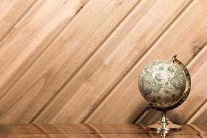 oude wereldbol tegen plank muur met kopie ruimte foto