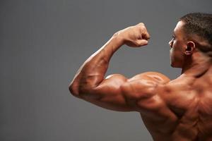 mannelijke bodybuilder buigen biceps, achteraanzicht met kopie ruimte