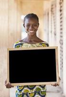 kopie ruimte: prachtige Afrikaanse etniciteit tiener schoolmeisje met schoolbord foto
