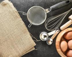 keukengerei en bakken ingrediënten op zwarte achtergrond, kopie-ruimte. foto