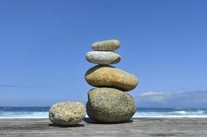 zen stenen gestapeld op het strand golven blauwe hemel kopie ruimte foto