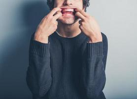 jonge man die gekke gezichten trekt foto
