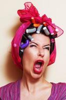 close-up van een jonge vrouw met haar krulspelden een grimas maken foto