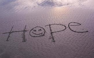 boodschap van hoop handgeschreven in glad zandstrand foto