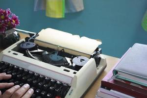 handen typen op oude typemachine foto