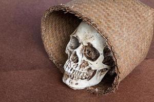 menselijke schedel in rieten mand foto