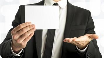 zakenman die witte kaart met exemplaarruimte houdt foto