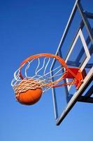 basketbal schot vallen door de netto, blauwe lucht foto
