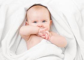 schattige baby liggend op een witte handdoek en zuigen eigen hand foto
