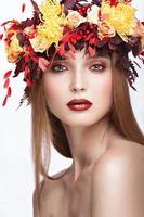 mooi roodharig meisje met heldere herfst krans van bladeren foto