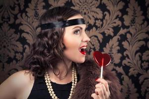 mooie retro vrouw met rode hartvormige lolly tegen foto