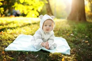 schattige blanke babyjongen in park kijkt naar de camera foto