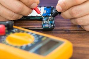 menselijke hand repareren van mobiele telefoon met multimeter foto