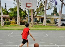 jongen speelt basketbal foto
