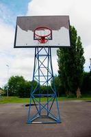 oude versleten basketbalring en blauwe hemel foto