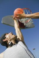 man basketbal spelen met vriend tegen hemel foto