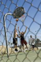 vrienden spelen basketbal op de baan foto