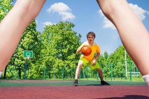jongen met bal die naar speler bij basketbal gaat foto