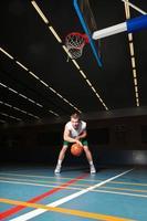stoere gezonde jonge man spelen basketbal in de sportschool binnen. foto