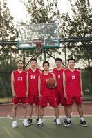 en basketbalteam die bevinden zich glimlachen, portret foto
