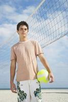 jongen staande op beachvolleybalveld foto