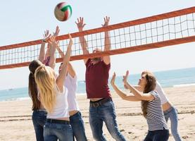 vrienden volleyballen op het strand foto