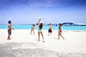 jongeren die volleyballen op een strand foto