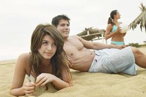 paar liggend op het zand door vriend met volleybal foto