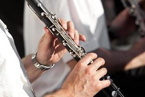 menselijke handen die een klarinet spelen foto