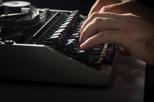 menselijke handen typen met typemachine foto