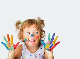 jong meisje met verf op haar handen en gezicht foto