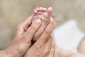 handen van een moeder die de voetjes van haar baby masseert foto