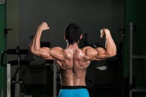 bodybuilder achter dubbele biceps poses uitvoeren