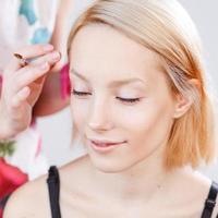 jong mooi meisje dat make-up toepast.