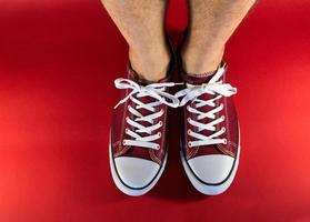 rode canvas sneakers en menselijke voeten foto