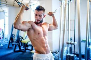 trainer, bodybuilder de biceps in de sportschool uit te werken