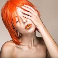 mooi meisje in een oranje pruik cosplay stijl