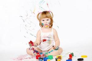 klein meisje bedaubed met felle kleuren foto