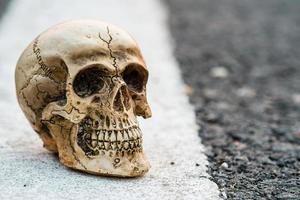 road death concept schedel op de straat van de asfaltweg foto