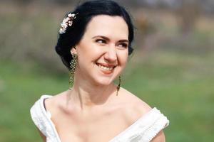 de gelukkige lachende bruid met bloemen in haar foto