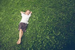 jonge jongen in het gras liggen en lachen foto