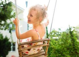 gelukkig meisje plezier op een schommel op zomerdag foto