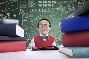 Aziatische jongen die in klasse met stapel boeken lacht foto