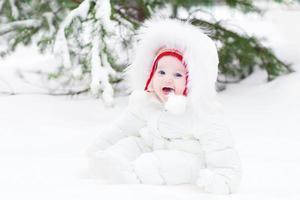 schattige lachende baby zitten in de sneeuw onder de kerstboom