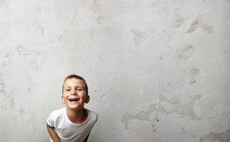 kleine jongen lachen om de camera. cocrete muur op een foto